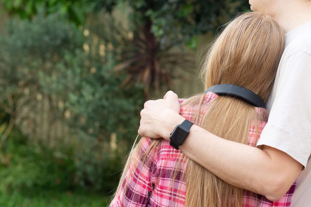 teenager leaning on Dad with his arm around her taken from behind to show their backs
