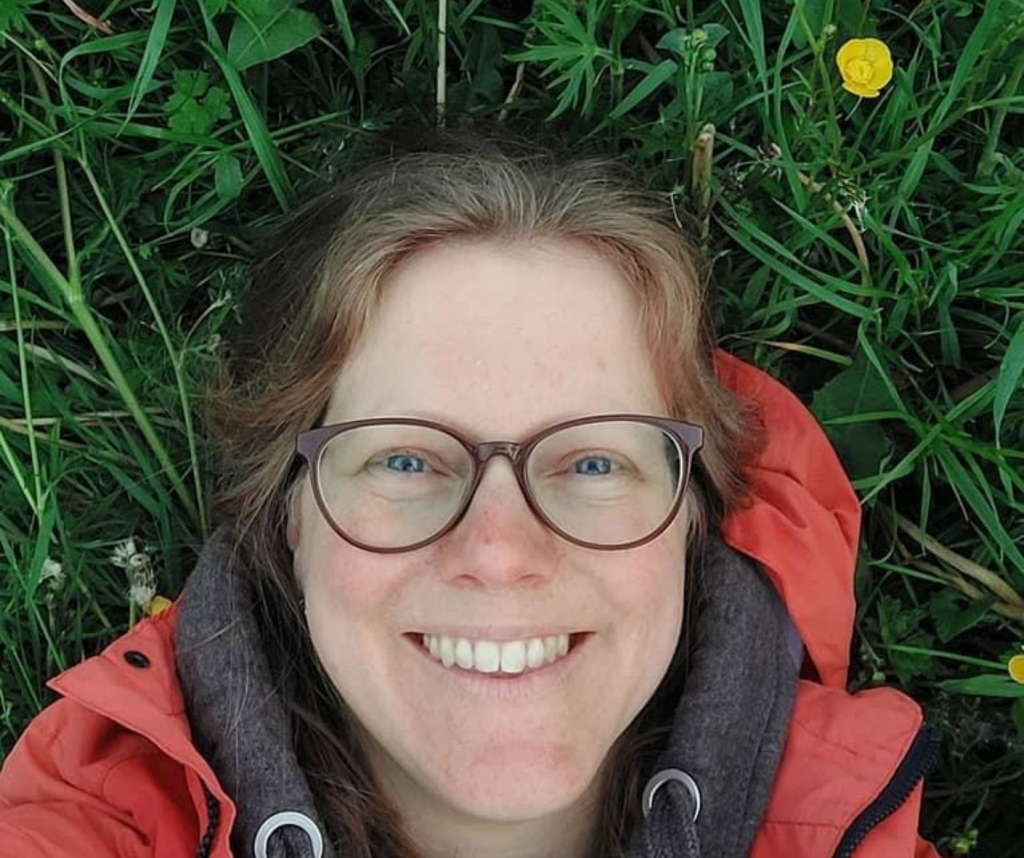Close up of Kate smiling and lying on the grass